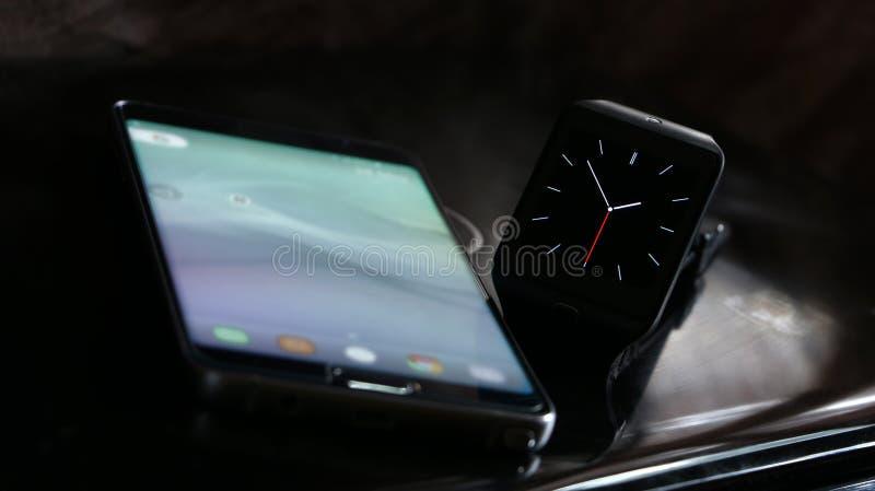 Smartwatch y smartphone fotos de archivo libres de regalías