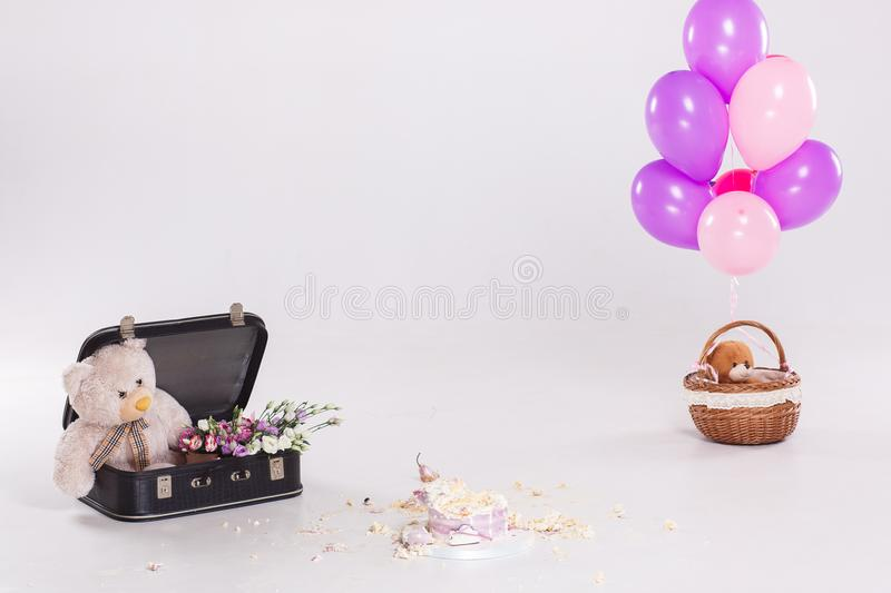 Smashed cake by baby on her first birthday party. Still life with teddy bear in suitcase, ballons. After party.  stock image