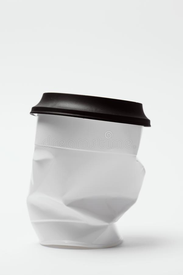 Smashed white plastic cup with lid royalty free stock photo