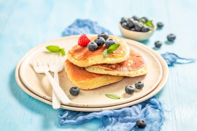Smaskiga amerikanska pannkakor med nytt blåbär och socker royaltyfri fotografi
