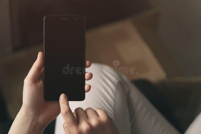 Smatphone teenager femminile della tenuta della mano all'interno con autenticazione di fabbricazione e dello schermo in bianco da fotografia stock libera da diritti