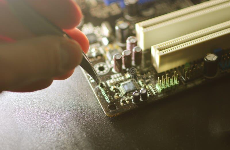 Smd elektronicznych składników tło Ręka z pincetami trzyma opornika na układzie scalonym zdjęcia royalty free