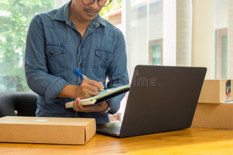 SME-företagsägare som kontrollerar inventarium med bärbara datorn på tabellen royaltyfria foton