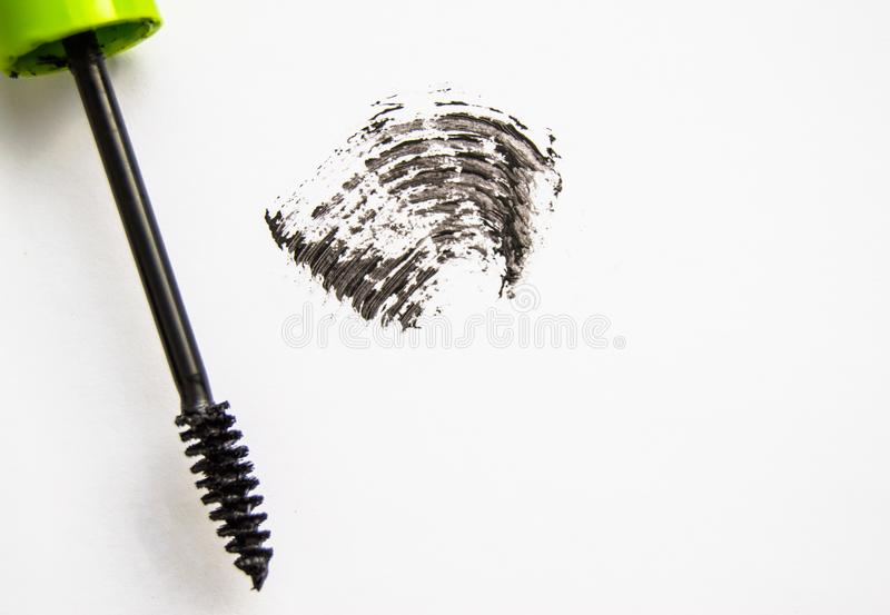 Smear and texture of black mascara isolated on white background with mascara brush. Paint, ink, stroke, beauty, makeup, applicator, close-up, cosmetics stock photo
