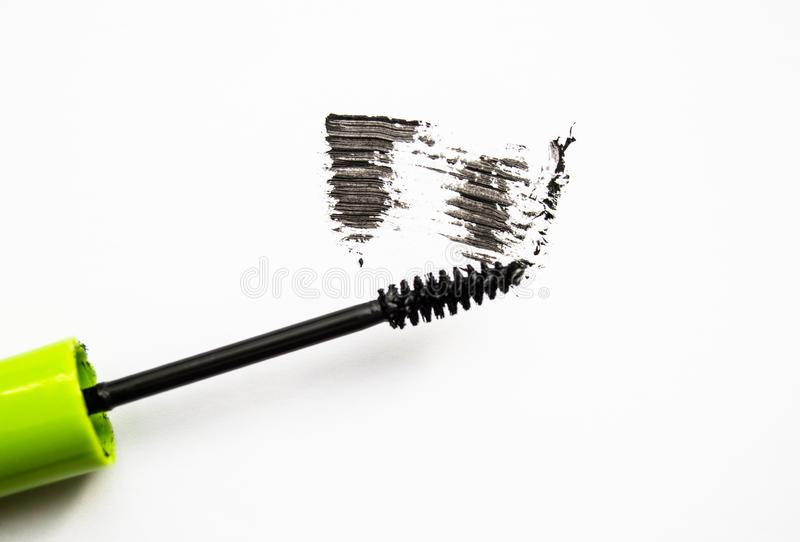 Smear and texture of black mascara isolated on white background with mascara brush. Paint, ink, stroke, beauty, makeup, applicator, close-up, cosmetics royalty free stock image