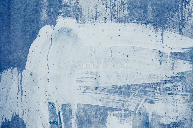 Smeared white paint stains on the blue wall. Drips of white paint on the blue canvas. Abstract pattern of spotted white stucco. Pa. Inted dirty concrete wall royalty free stock photo