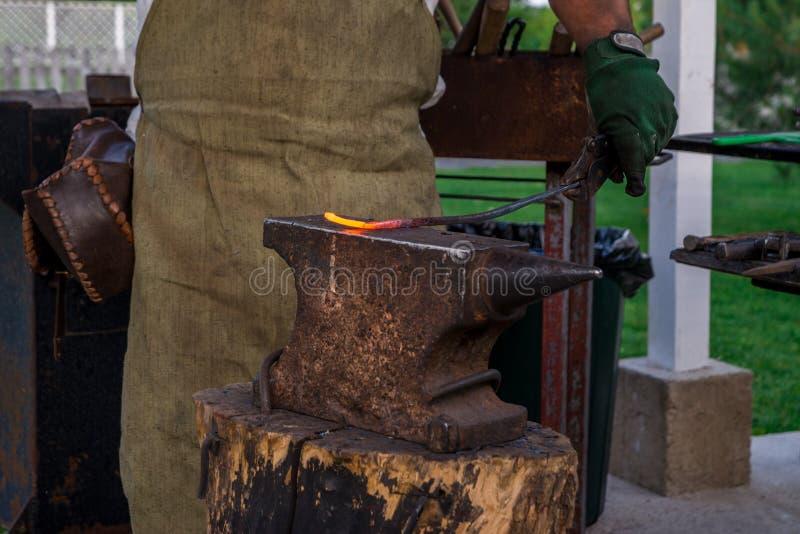 Smeden rymmer en metallstång värmd till smältning på städet, befo royaltyfri bild