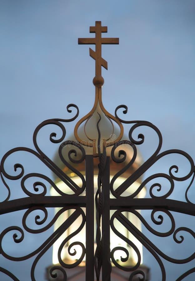 Smeedijzeromheining en een kruis op de koepel van witte steen orthod royalty-vrije stock afbeelding