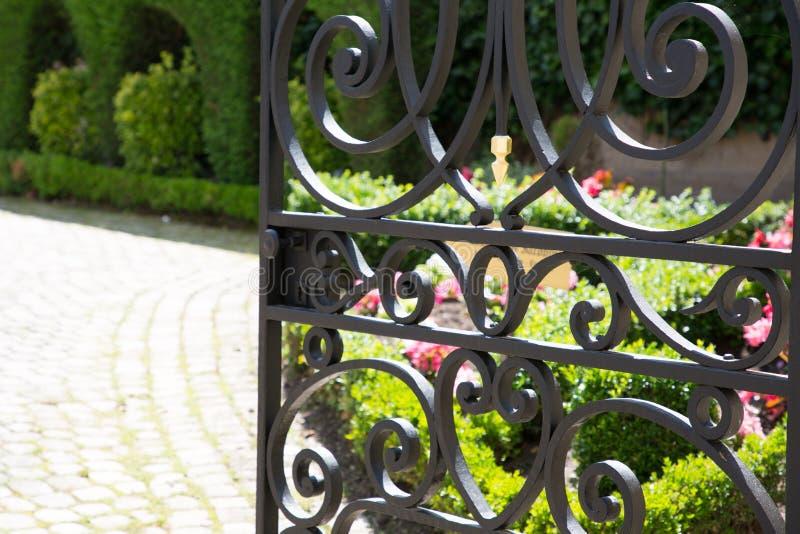 Smeedijzerpoort open aan de tuin en zijn plakoprijlaan stock afbeeldingen