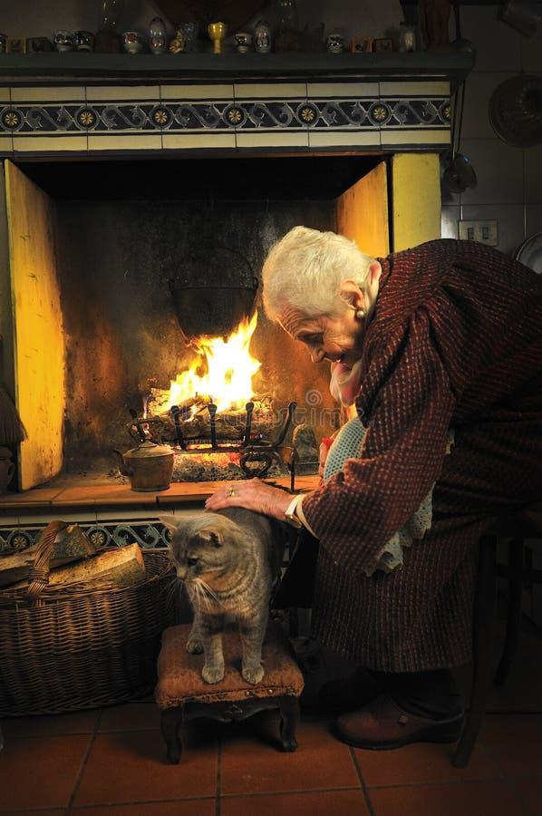 smeka katten henne gammal kvinna arkivbild