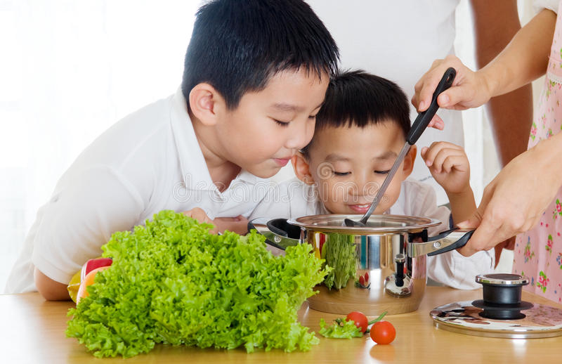Smell. Asian boys smell their mother's cooking royalty free stock photography
