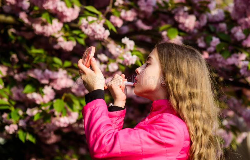 Smell of tender bloom. Sakura flower concept. Gorgeous flower and female beauty. Natural cosmetics for skin. Girl in. Cherry flower. Kid with lipstick makeup royalty free stock photos