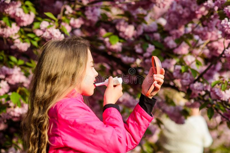 Smell of tender bloom. Sakura flower concept. Natural cosmetics for skin. Girl in cherry flower. Kid with lipstick. Makeup. Small girl child in spring flower royalty free stock images