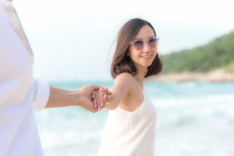 Smelling Couple summer Vacation, Asian young woman holding man hand on the beach, so happy and in love on honeymoon holiday royalty free stock photography