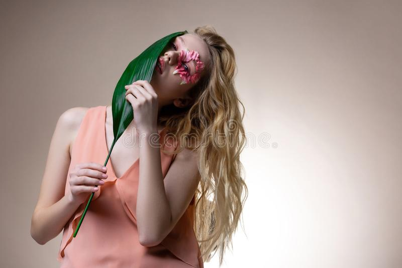 Blonde-haired model feeling good while smelling green leaf stock images