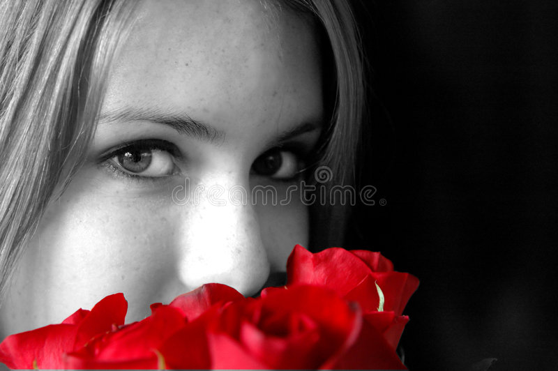 Smelling red roses. A profile of a pretty girl smelling roses in black and white with roses colored red stock image