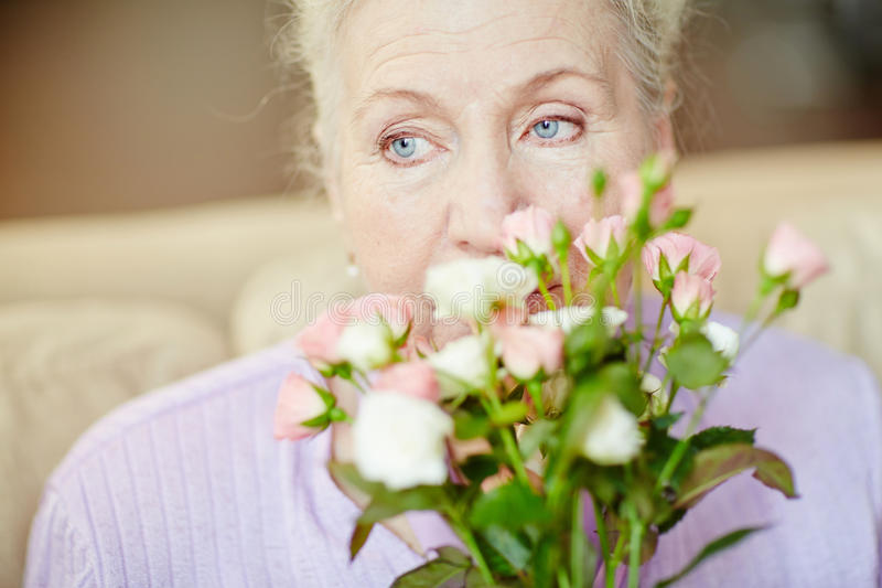 Smelling roses. Elderly woman smelling fresh roses royalty free stock photography