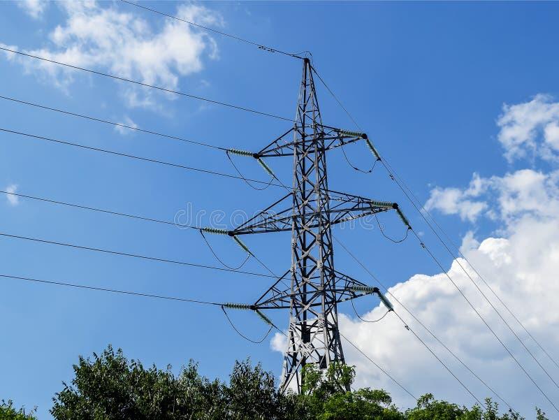 Smelt de machts pylon en met hoog voltage draden met glas tegen een heldere blauwe hemel met witte wolken op een zonnige dag De m stock fotografie