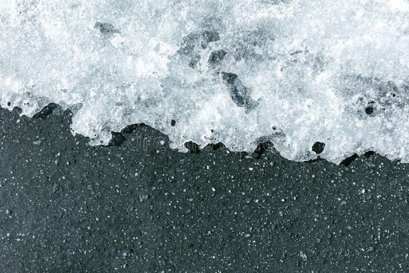 Smeltend ijs op asfalt in de lente Smeltende sneeuwachtergrond stock afbeeldingen