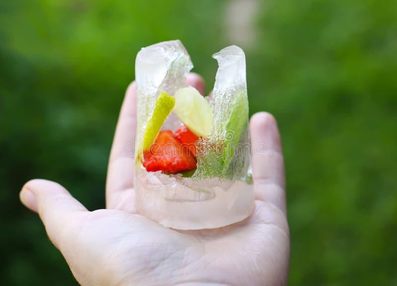 Smeltend ijsblokje met aardbei, citroen en verse groene muntbladeren royalty-vrije stock foto