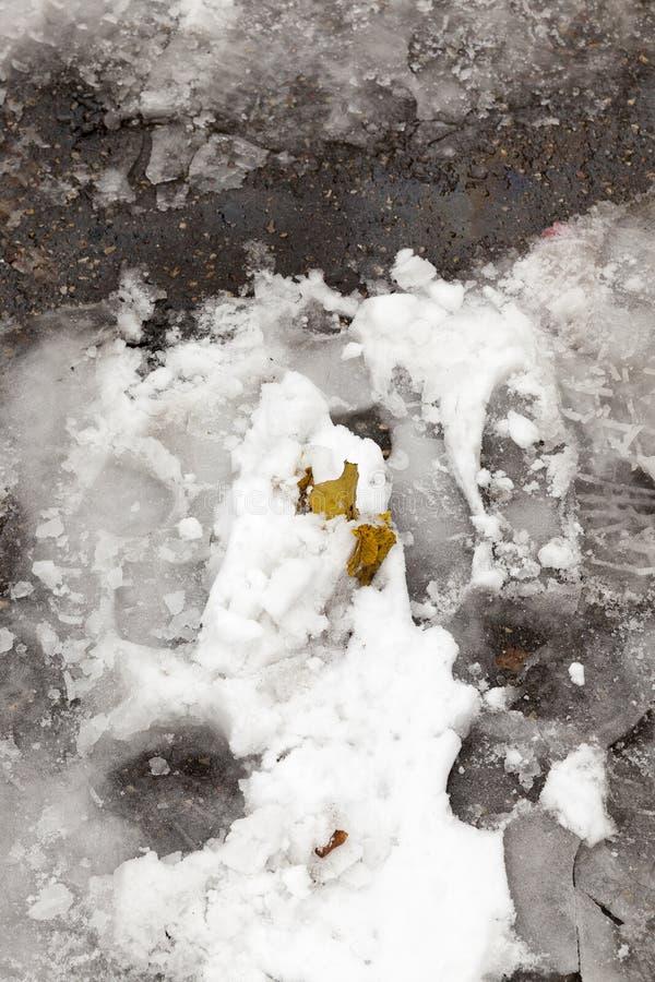 Smeltende de sneeuwbladeren van de asfaltweg stock foto