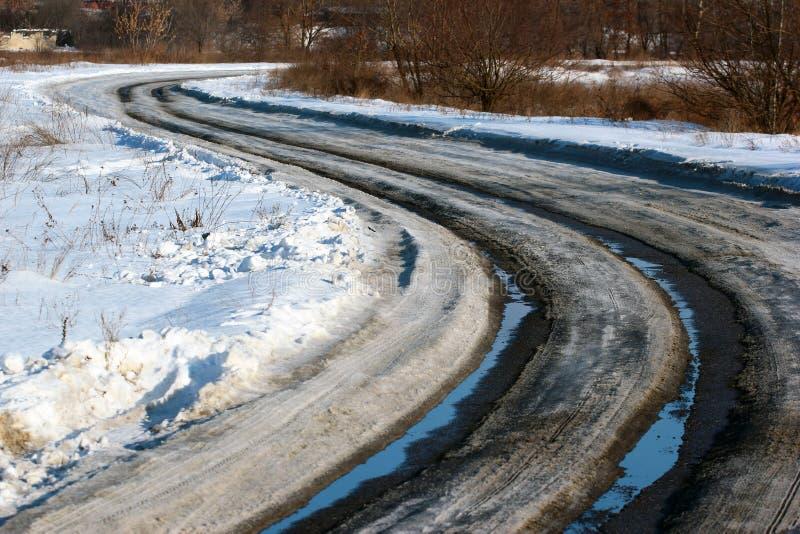 Smeltende sneeuw en sneeuwbrij op een windende asfaltweg bij de winter royalty-vrije stock foto's