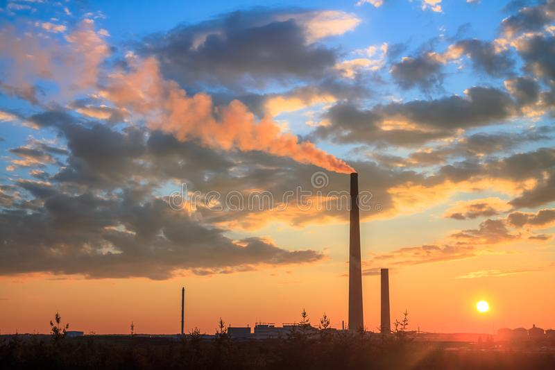 Smelter stack of a nickel plant. View of a smelter stack of a nickel plant showing the emission on the air with sunset sky as as background royalty free stock photos