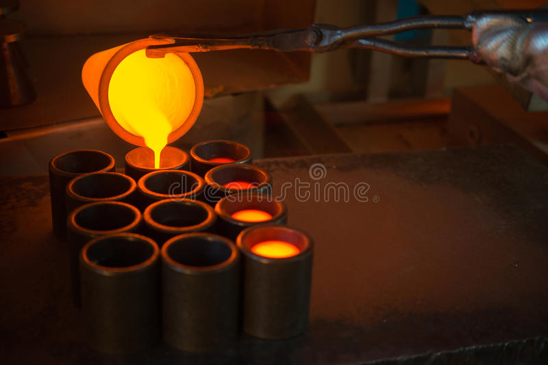 Smelting gold at a factory. Pouring melted gold in the metal form at a factory stock images