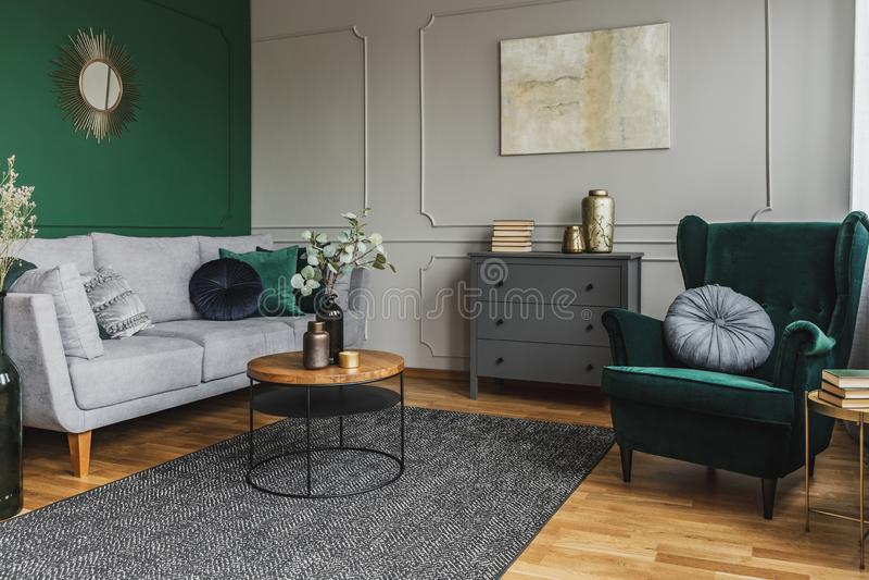 Smeraldo seggiolino verde con cuscino in salotto grigio all'interno con comodità di legno fotografie stock libere da diritti