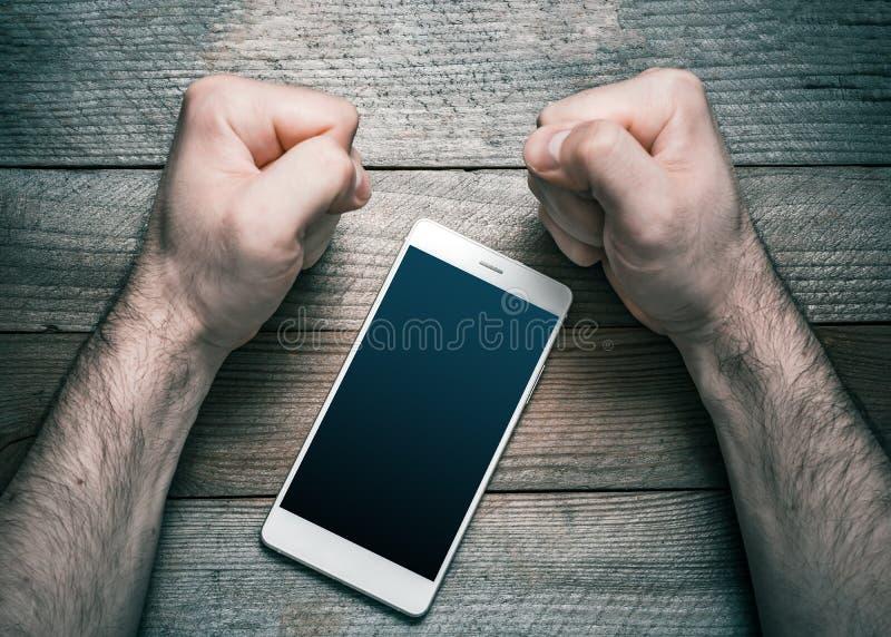 Smesso facendo uso di Smartphone o del concetto sociale di media con un telefono cellulare bianco circondato da 2 pugni chiusi di fotografie stock libere da diritti
