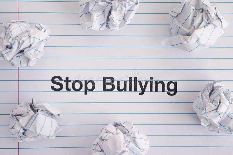 Smetta di opprimere Esprima la fermata che opprime sullo strato del taccuino con alcune palle di carta sgualcite su  fotografie stock