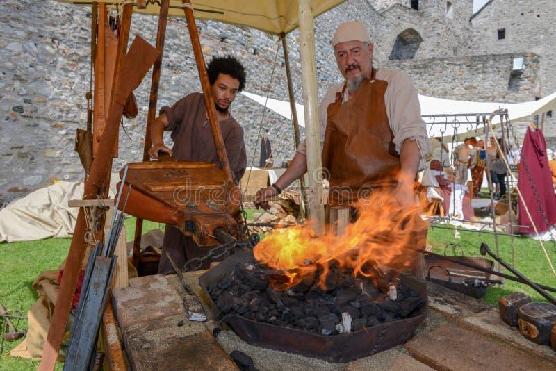 Smid die een zwaard bij de middeleeuwse markt smeedt royalty-vrije stock foto's