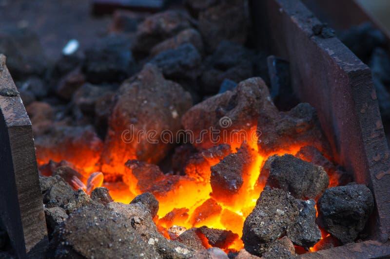 smidsoven met het branden van steenkolen, hulpmiddelen, en het gloeien van hete metaalwerkstukken stock afbeelding