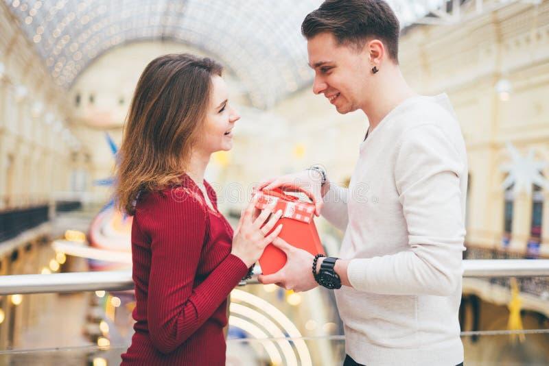 Smilande pojke som ger en present till sin flickvän på Valentindagen royaltyfria bilder
