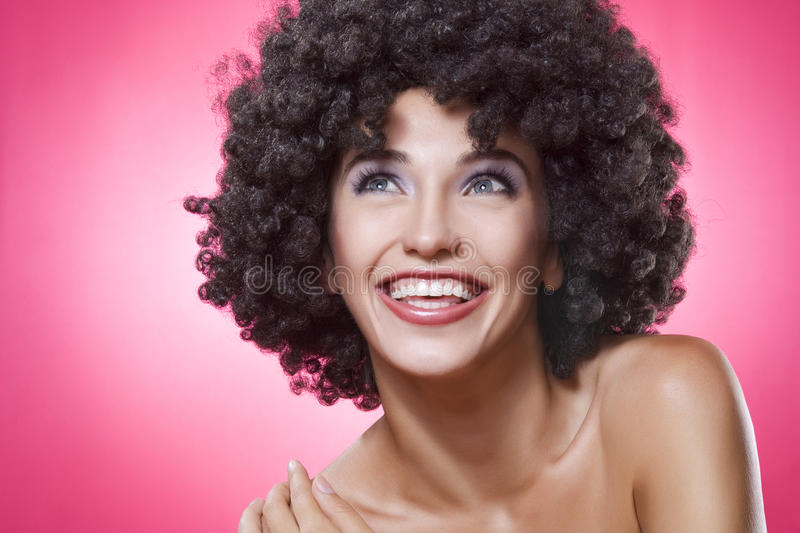 Smile. Close up portrait of young woman in afro wig on pink back royalty free stock images
