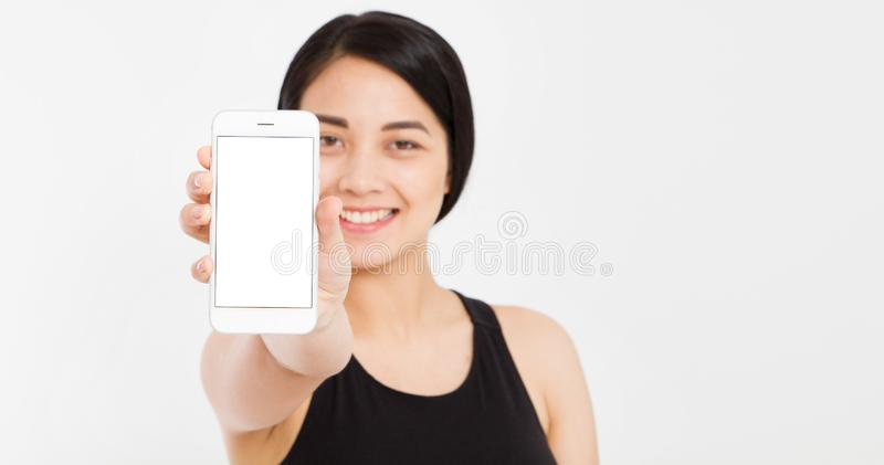 Smile asian girl show empty blank screen mobile phone - selective focus on cellphone royalty free stock photo