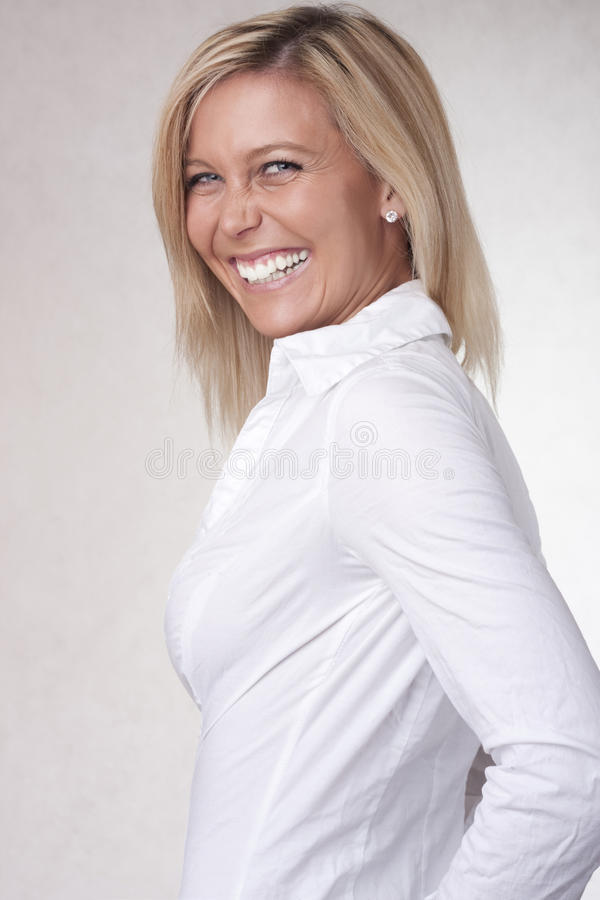 Smile beautiful blond girl in white chemise royalty free stock photography