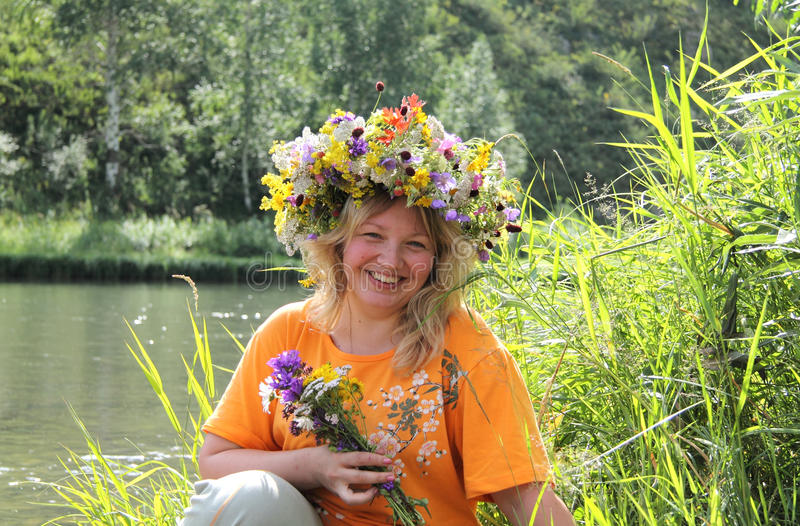 Smile of the beautiful woman in a flower wreath stock photography