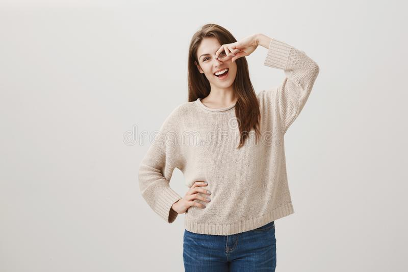 Smile brightens every mornings. Studio shot of positive friendly caucasian female brunette holding hand on hip and. Showing sign over eye, smiling broadly stock image