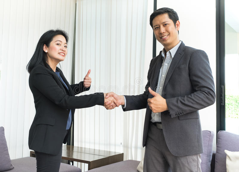 Smile Business woman and business man shaking hand and thumb up. Smile Business women and business men shaking hand and thumb up in office ,Partnership agreement royalty free stock images