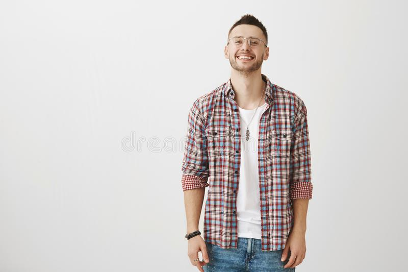 Smile can break ice. Studio shot of good-looking young man with bristle in transparent glasses grinning while being very royalty free stock photography