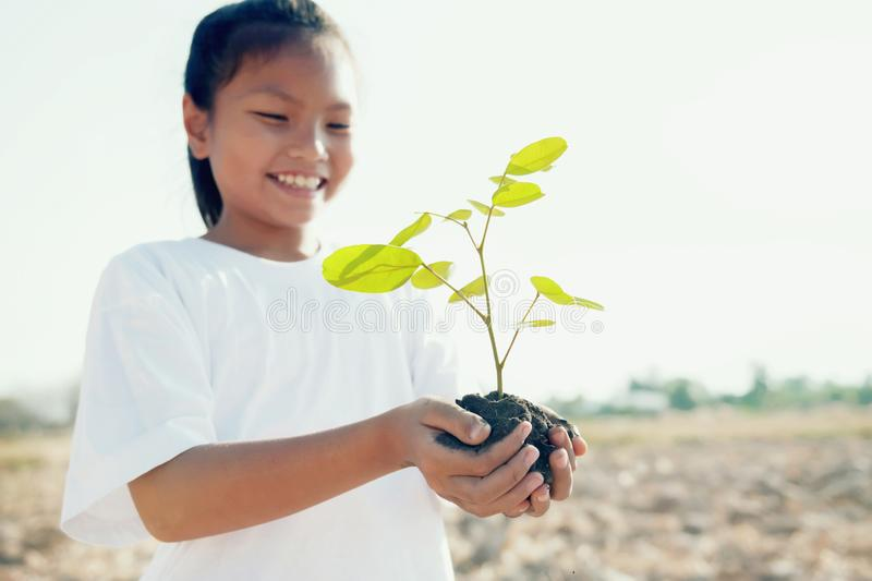 Smile children holding young tree for planting. Concept save world royalty free stock photos