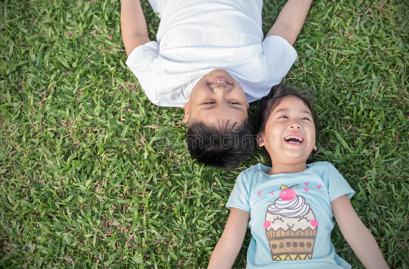 Smile children lie down on grass royalty free stock images