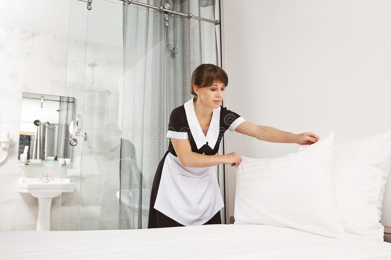 Smile of client makes me feel better. Female in maid uniform making bed in bedroom, putting pillow after previously stock photo