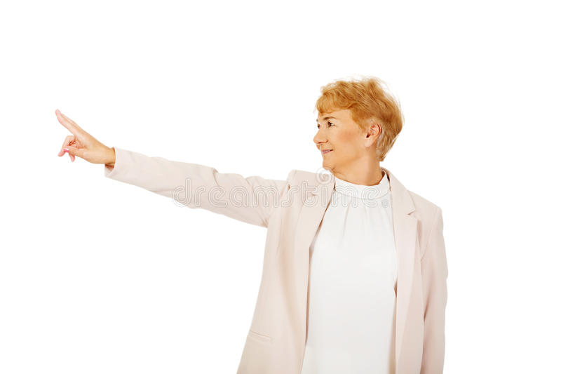 Smile elderly business woman pointing for copyspace or something royalty free stock photo