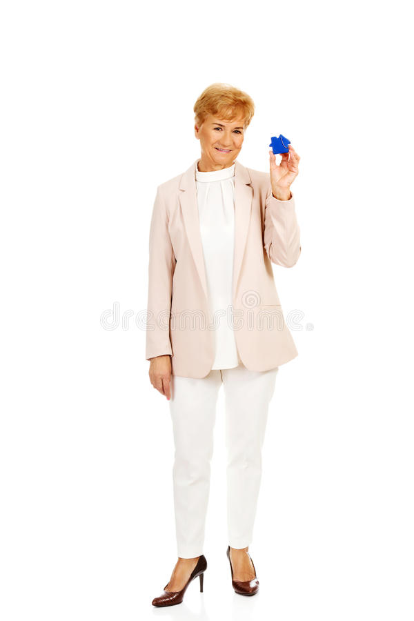 Smile elderly woman holding blue key pendant royalty free stock photography