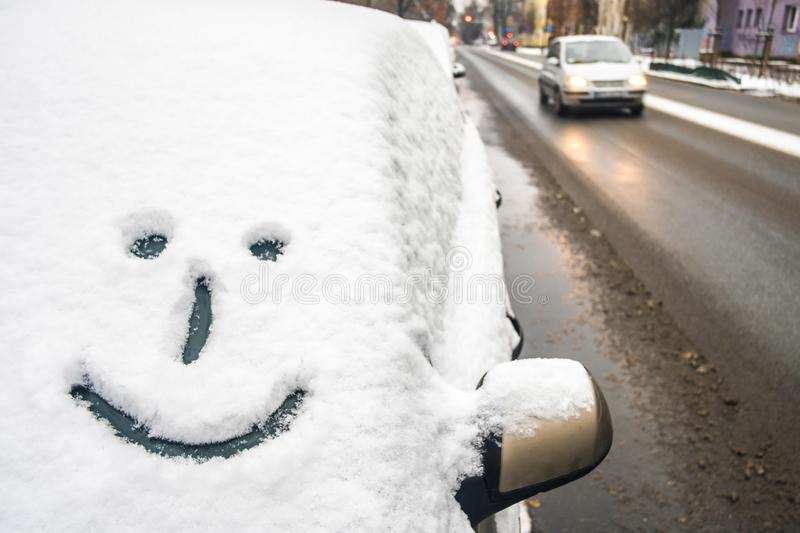 Smile emoji on the car front window, drawing in snow, positive mood and happiness stock photography