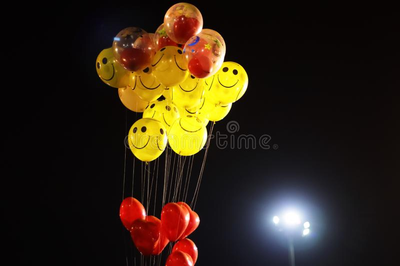 smile emoji shaped yellow balloon and heart shaped red balloons tied in bunch with threads in black background royalty free stock image