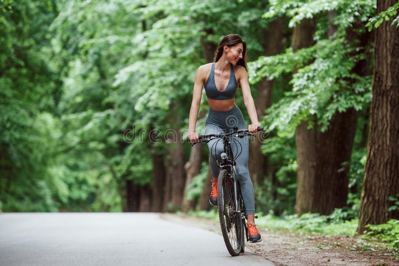 With smile on the face. Female cyclist on a bike on asphalt road in the forest at daytime royalty free stock images