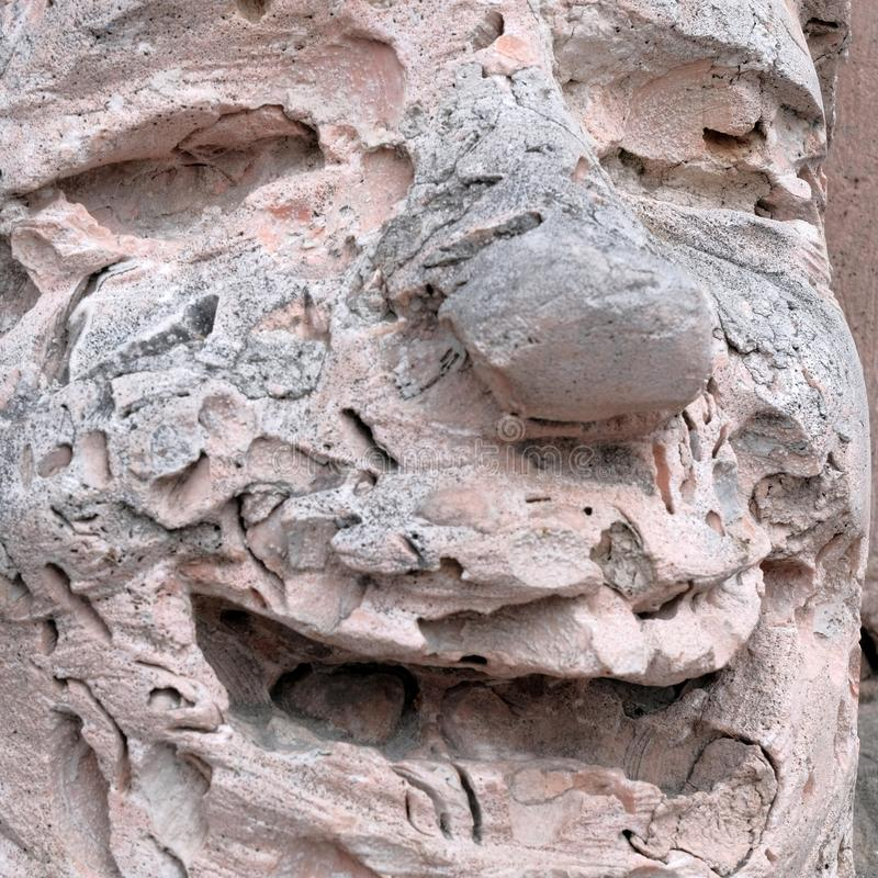 The face of a cheerful stone man. The smile on the face of the sculpture. Texture of pink shell rock. The smile on the face of the sculpture. The face of a stock image
